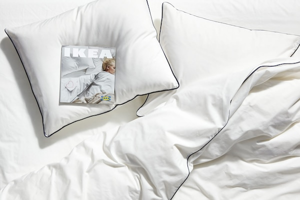 Bijeli jastuci na krevetu s bijelim navlakama i kopija IKEA Kataloga 2020. ostavljenog na jednom od jastuka.