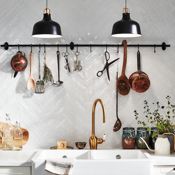 Bijeli zid s pločicama s FINTORP šipkom s kukama montiranom na zid. Začinsko bilje, kuhinjski pribor i ukrasni predmeti obješeni su na njoj.
