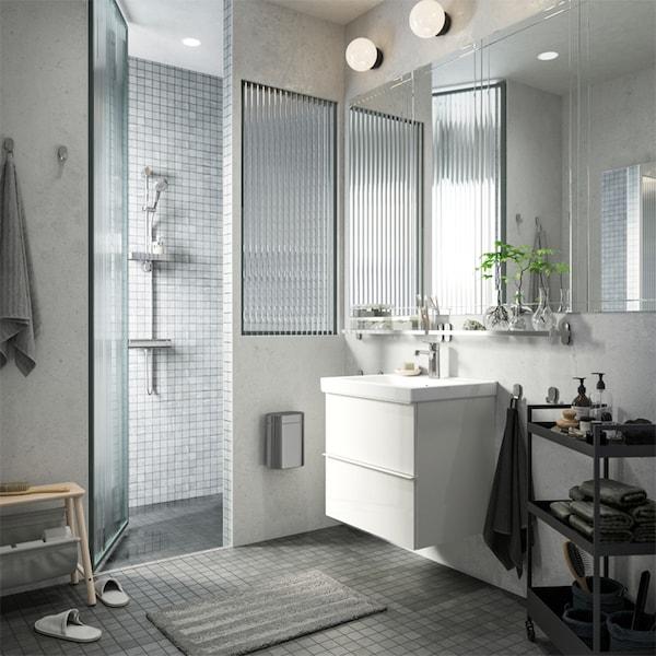 Bijelo-siva kupaonica s tušem, bijelim umivaonikom i crnim kolicima na kojima se nalaze ručnici, sapuni i još mnogo toga.