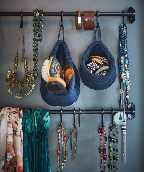 Bijoux et accessoires suspendus à des rails fixés sur un mur bleu.