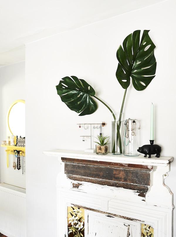 Bijoux et plantes présentés sur une cheminée.