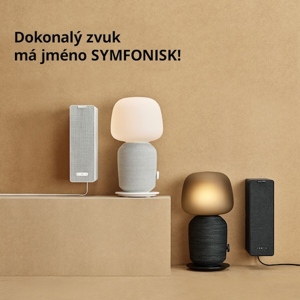 bílá a černá lampa SYMFONISK s reproduktorem a extra reproduktorem zavěšeným na zdi.