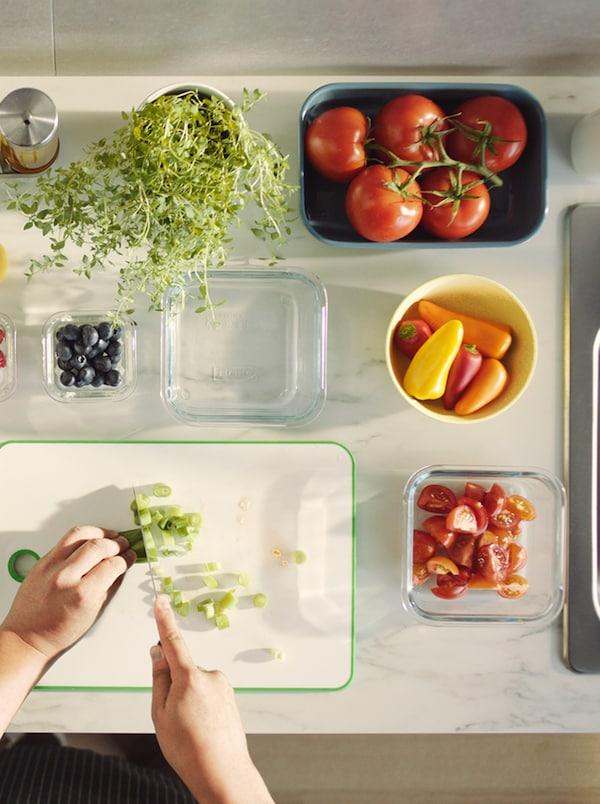 Bílá deska, na které někdo krájí zeleninu, akolem jsou rozmístěné skleněné aporcelánové nádoby sovocem azeleninou.