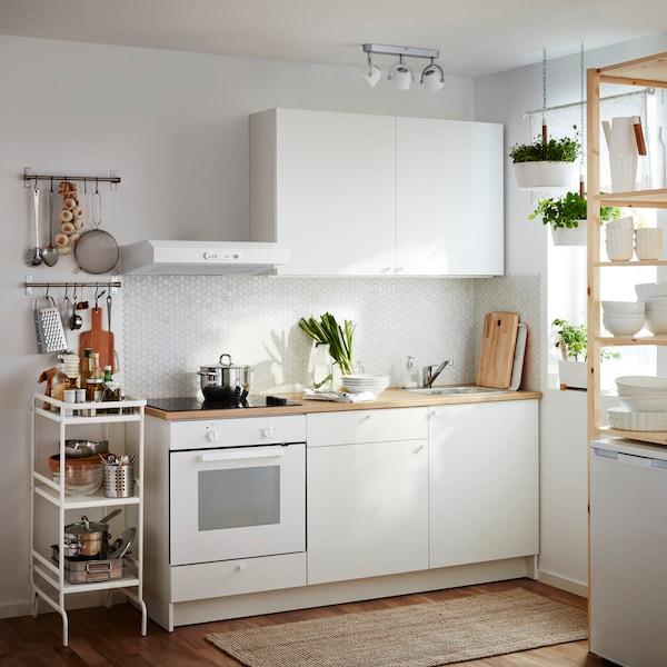 Bílá kuchyně KNOXHULT s dřevěnými pracovními deskami, chladničkou.