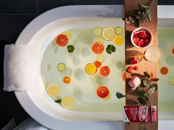 Bílá vana napuštěná teplou vodou, v níž jsou plátky citrusů a bylin, na prkénku přes vanu je zdravé občerstvení a růže