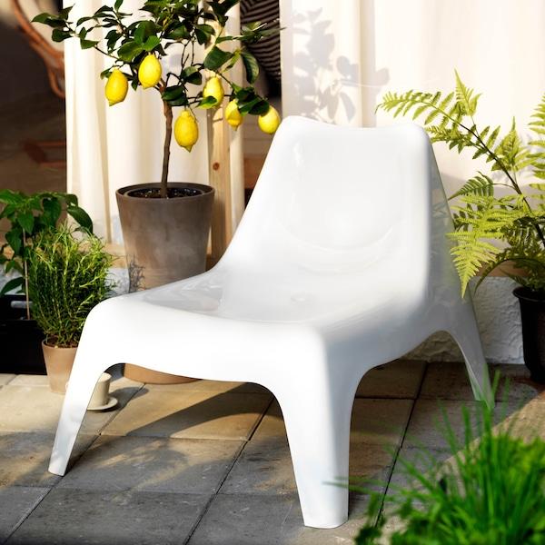 Bílá zahradní židle obklopená zelení.