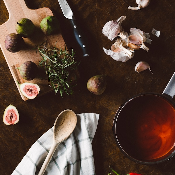 Bild ovanifrån på en skärbräda med fikon, kastrull med tomatsås och vitlöksklyftor