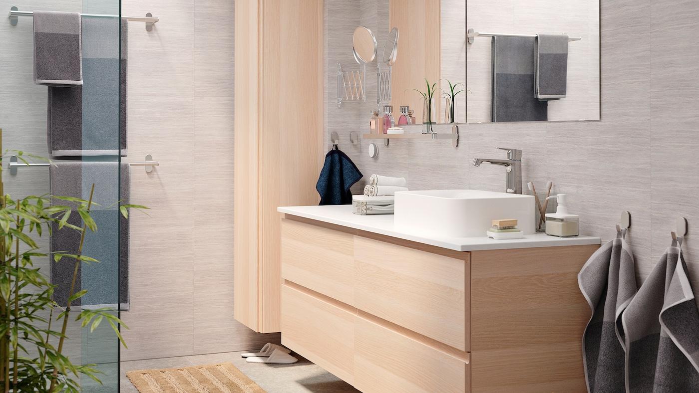 Bilik mandi yang cerah dan elegan dengan kabinet sink GODMORGON dan kabinet tinggi GODMORGON dalam kesan kayu oak berwarna putih.