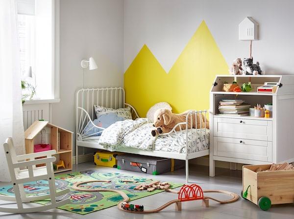 Bilik tidur kanak-kanak dengan katil boleh dipanjangkan MINNEN disandarkan ke dinding di sebelah meja tukar lampin SUNDVIK. Set kereta api berada di atas lantai.