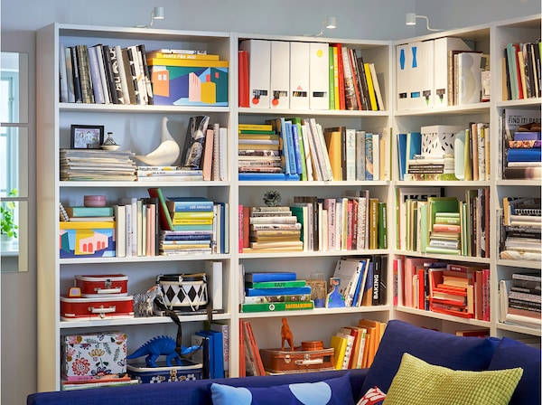 BILLY bookcase with adjustable shelves, situated in the corner of a living room and filled with books, photos and ornaments.