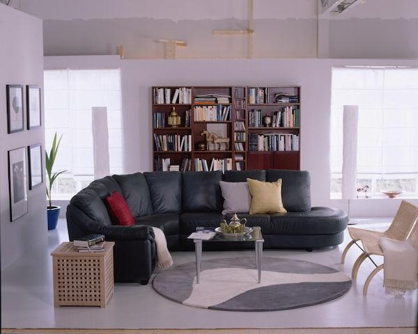 BILLY kirjahylly 1980-luvulla. Nahkasohva ja pyöreä, kuviollinen matto täydentävät 80-lukuisen tyylin.