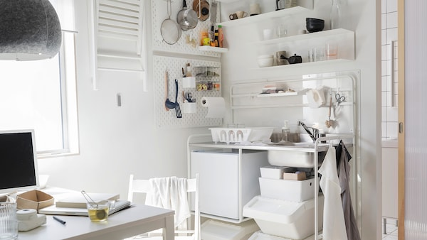 Bílý kuchyňský kout s bílou minikuchyní SUNNERSTA, malou bílou ledničkou, bílým stolem a jednou bílou židlí.