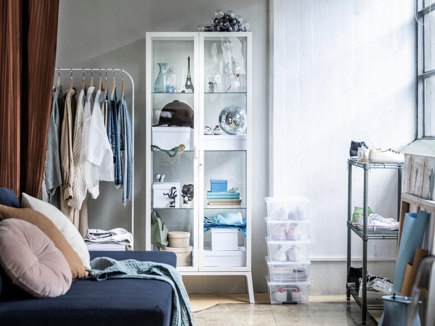 Bílý pokoj s modrou pohovkou a bílým šatním stojanem MULIG, u zdi stojí bílá vitrína MILSBO. Na podlaze leží několik průhledných krabic SAMLA.