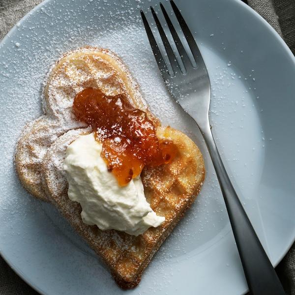 Bílý talíř svidličkou advěma vaflemi se šlehanou zakysanou smetanou amoruškovým džemem. Vafle jsou posypané moučkovým cukrem.