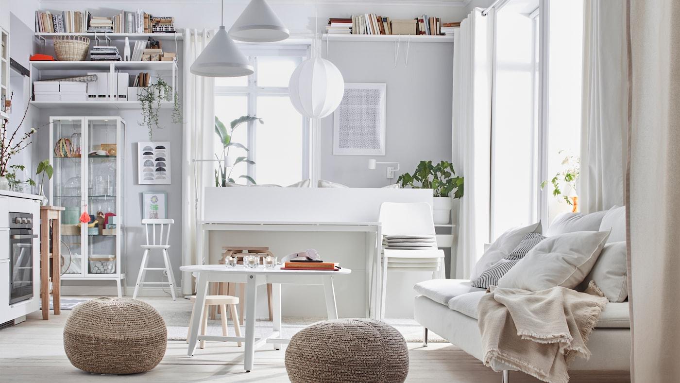 Binnenkant van een studio in lichte kleuren: bed, zetel, kitchenette, opbergruimte en twee SANDARED poefjes.