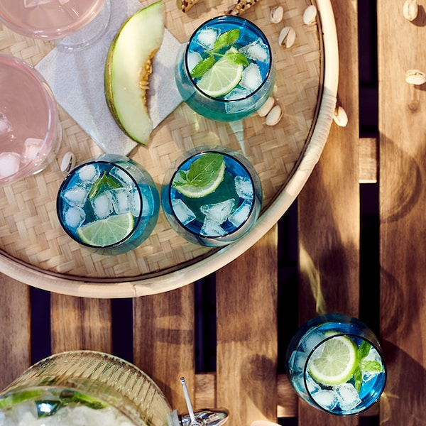 Bird's eye view of a picnic table, with a round tray containing blue glasses filled with iced water and slices of lime.