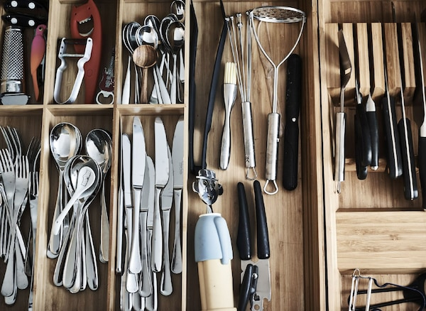 Bird's-eye view of cutlery sorted in kitchen drawer inserts.