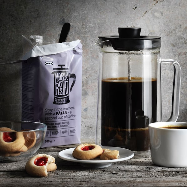 Biscuits with raspberry filling sit on a plate, in a bowl and on the table next to a cup of coffee. PÅTÅR coffee in a french press next to its packaging is in the foreground.