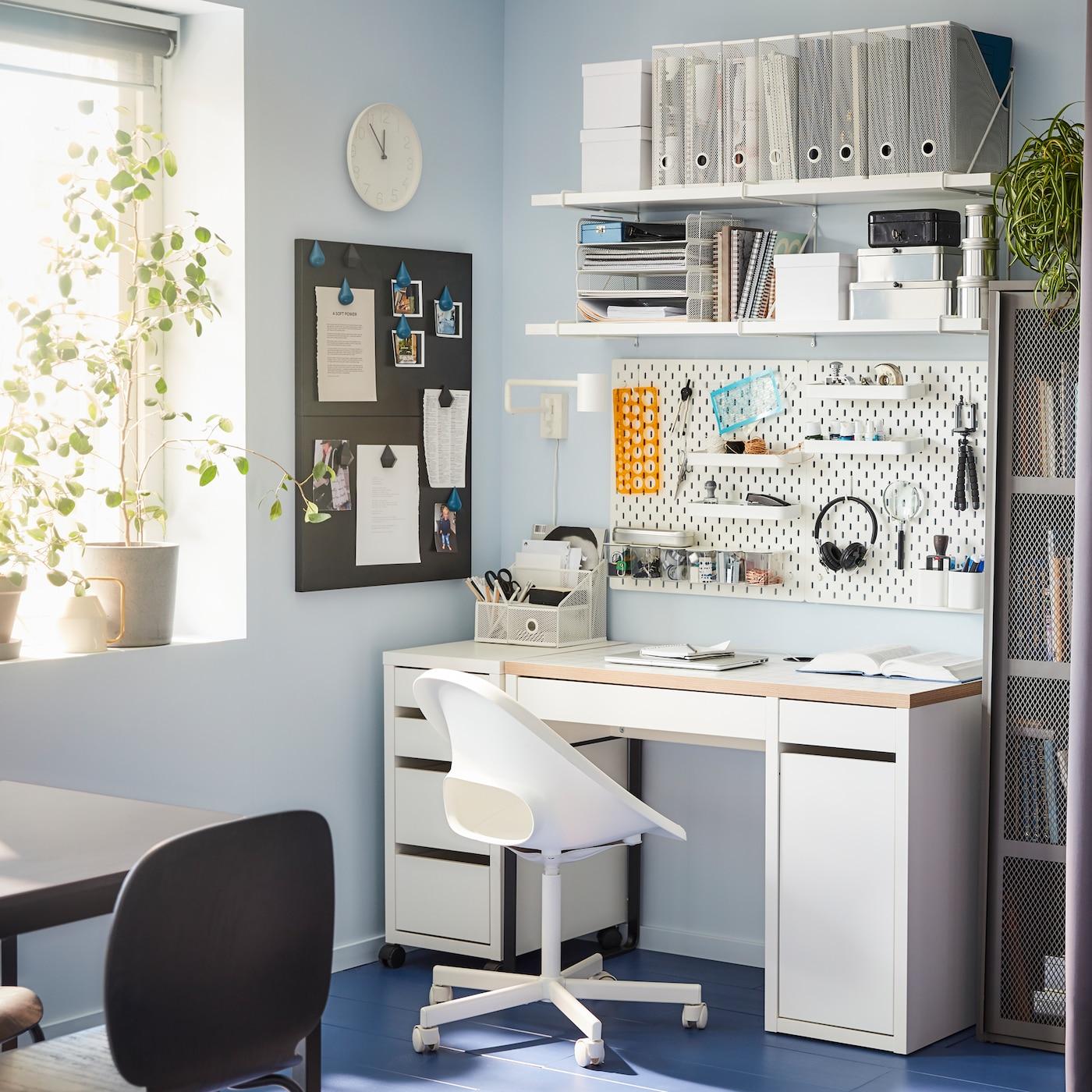 Biurko, krzesło obrotowe, dwie półki ścienne i tablica perforowana w kolorze białym, szara szafka i okno z szarą roletą.