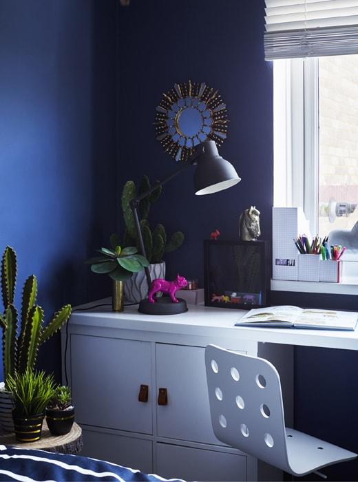 Biurko z miejscem do przechowywania i lampą.