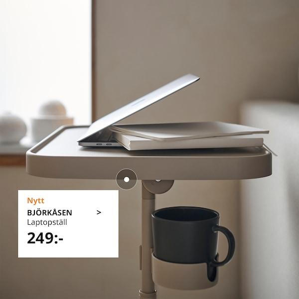 BJÖRKÅSEN laptopställ med en dator och kopp på.