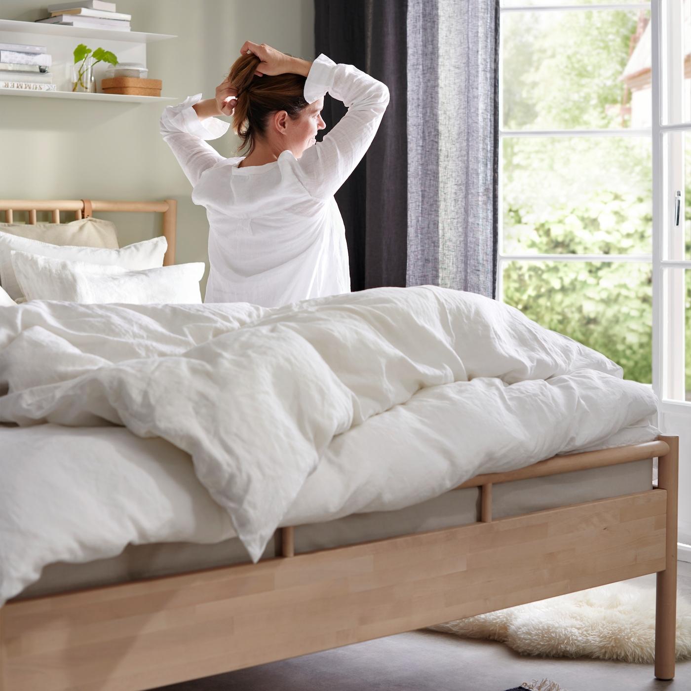 BJÖRKSNÄS säng står vid en öppen balkongdörr bäddad i vitt.