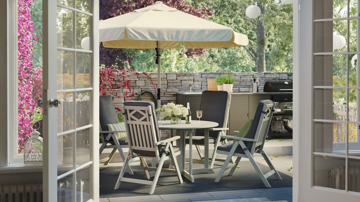 ベージュのパラソルを立てた屋外用テーブル、リクライニングチェアとダークグレーのクッション、レンガ壁のフェンス、屋外キッチン。