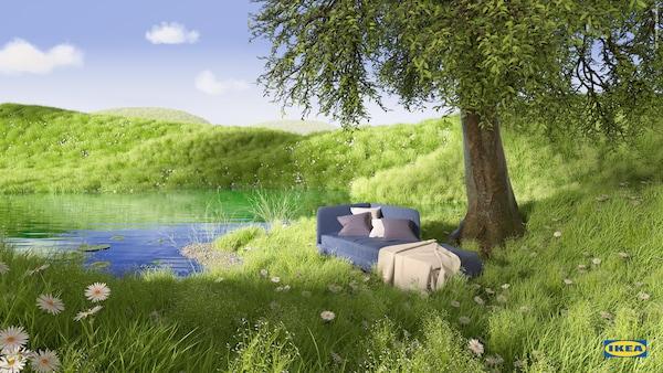 Blå BLÅKULLEN sengestamme med hodegavl i hjørnet, pledd og puter i ei frodig blomstereng ved en dam og et tre.