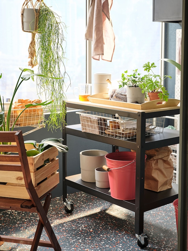 Black and pine utility cart on wheels in an outdoor space.