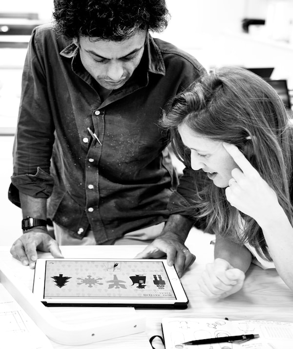 Black-and-white image of a man and a woman huddled over a digital tablet, both focused on illustrations on its screen.