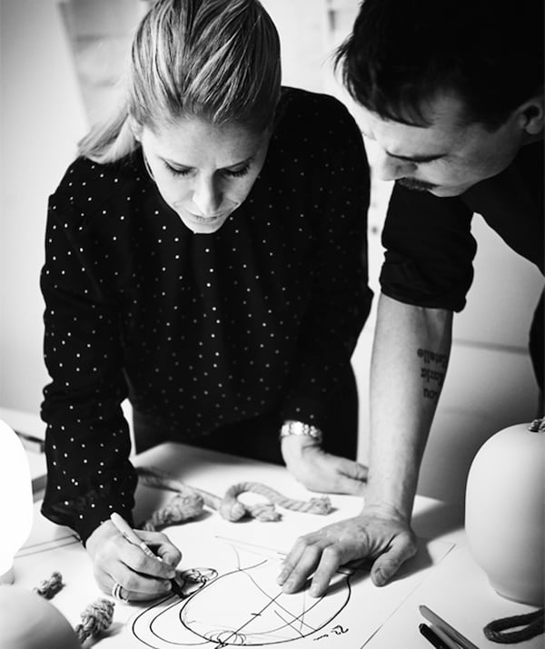 Black-and-white image of a woman and a man standing huddled over a table, both focused on a sketch the former is drawing.