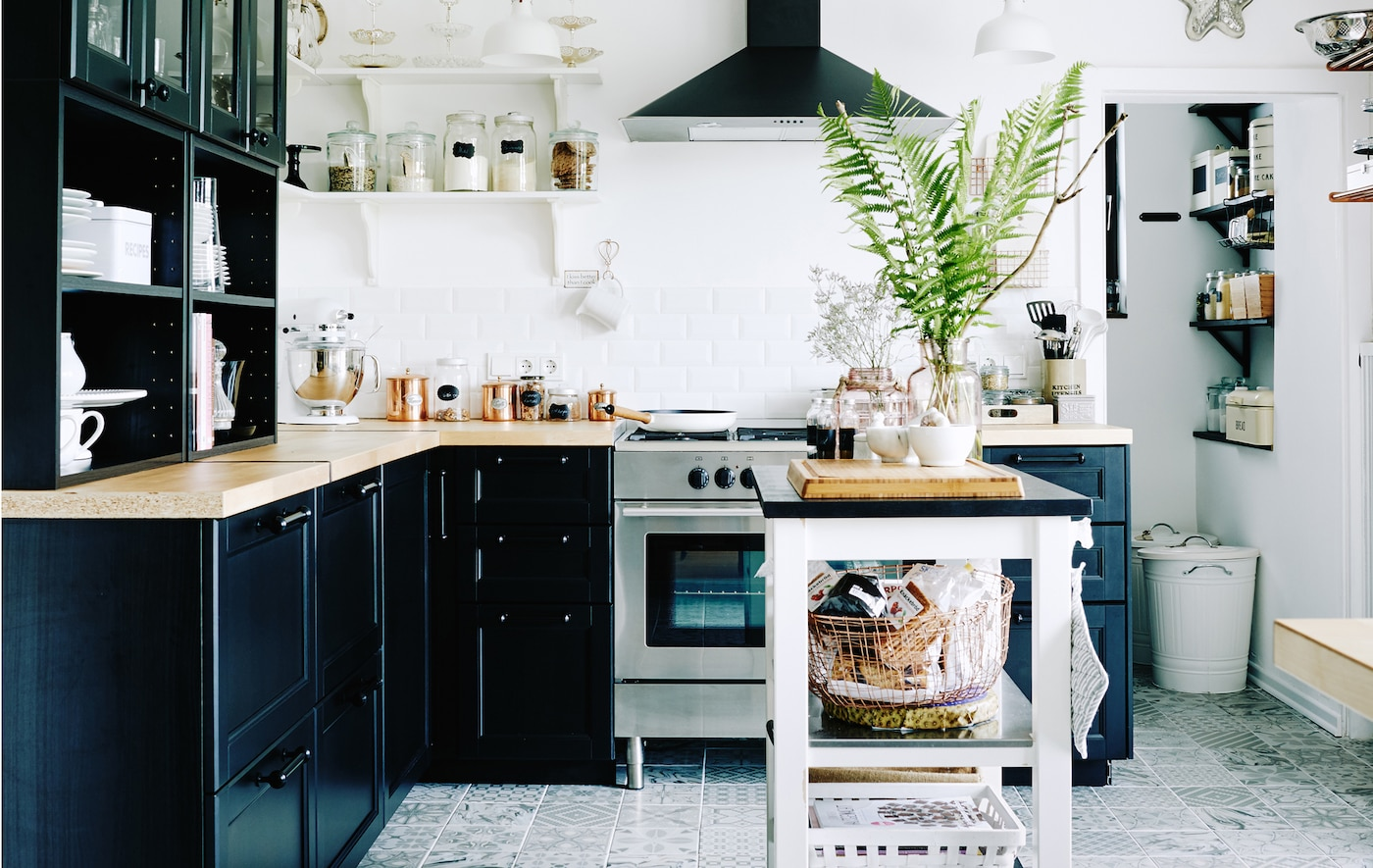 Black and white kitchen with pantry area packed with storage solutions.