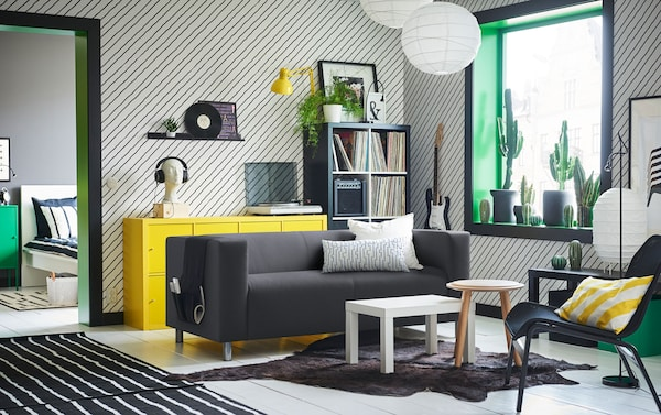 Black and white sofa with leaf motif in the centre of a black, green and yellow living room with diagonal striped walls.