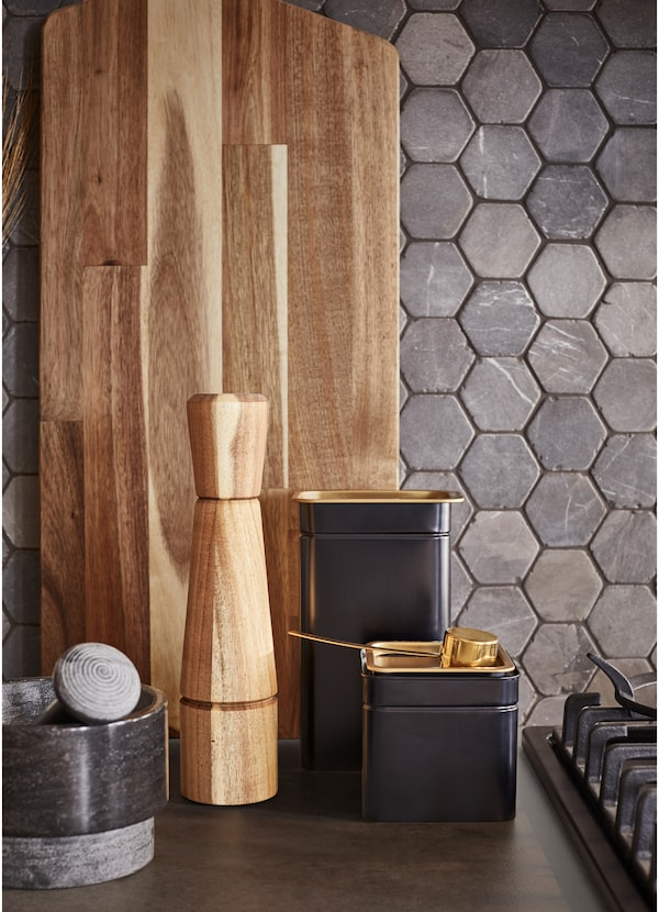 Black, brass, stone, metal and hearty wood textures in kitchen accessories, including a mortar and pestle, chopping board and pepper shaker.