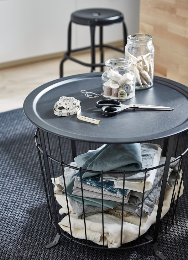 Black coffee table with wired basket bottom and removable tray tabletop, holding scissors and sewing supplies on top.