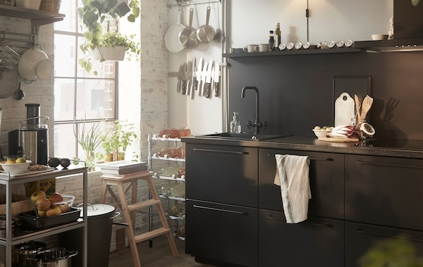 Black kitchen cupboards with a sink, a metal trolley and utensils stored on rails by a window.