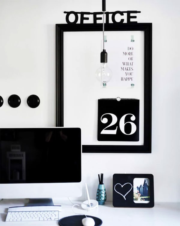 Black picture frame turned into a memo board on the wall behind a computer
