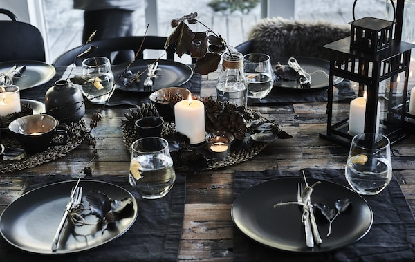 Black plates, steel cutlery, tumblers and a centrepiece created of a lit block candle and pine cones on a woven placemat.