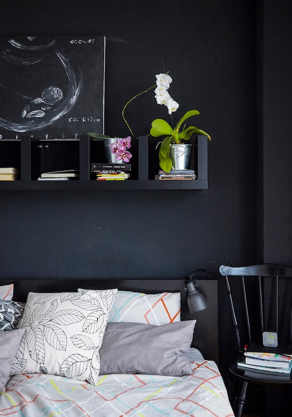 Black shelves above a bed, holding plants and books.