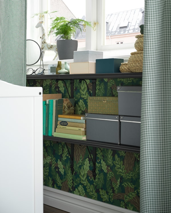 Black shelves are wall-mounted under a window and used as a bedside table. Books, boxes and decorative items stand here.