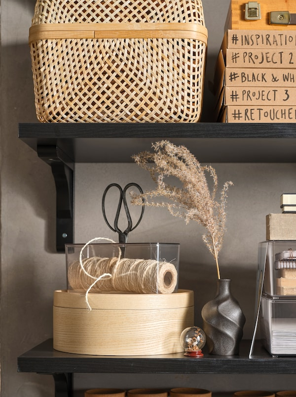 Black shelves with a SMARRA storage box in bamboo, a round MALLGRODA box and personal items for work and display.