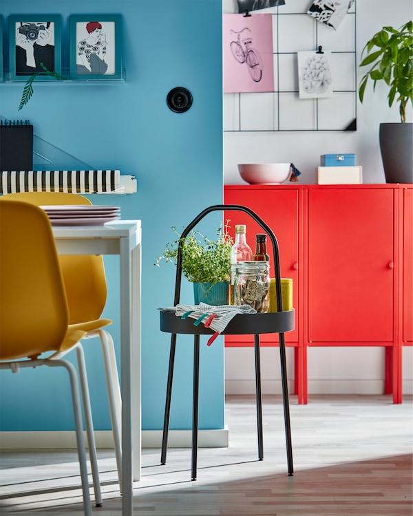 Black side table with handle, yellow chairs, white table, blue frames, red cabinet and a wall-mounted black memo board.