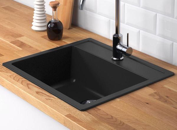 Black sink in a kitchen with chopping block countertops