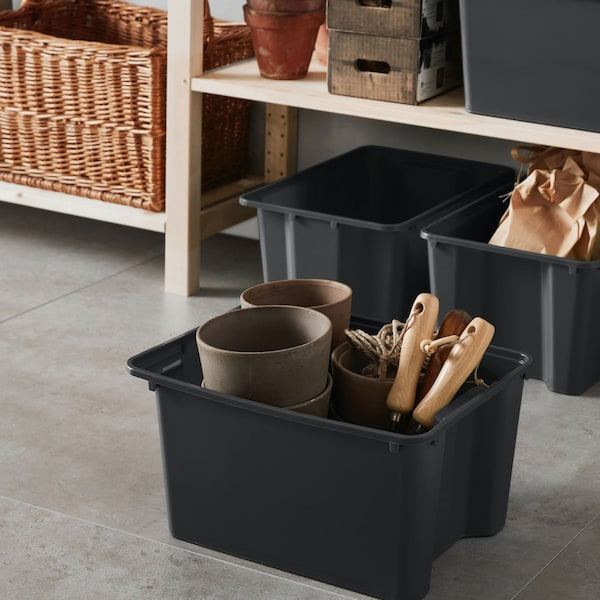 Black storage box sitting on floor of garage with gardening tools inside