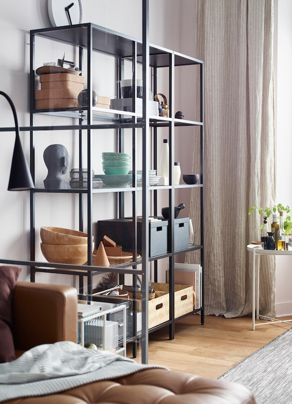 Black wired open storage shelf, holding boxes, bowls and statues in a dining room area.