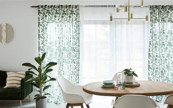 Blagovaonica s drvenim stolom i bijelim stolicama ispred francuskih prozora na kojima se nalaze zavjese bijele boje s uzorkom lišća.