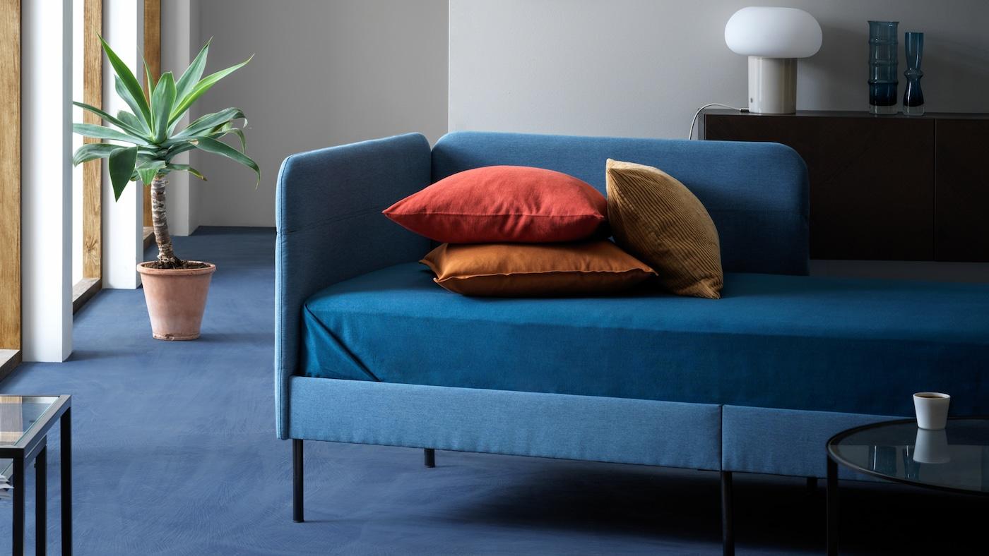 BLÅKULLEN БЛОКУЛЛЕН каркас ліжка з м'якою оббивкою з подушками в натуральних відтінках стоїть у прохолодній добре освітленій вітальні.