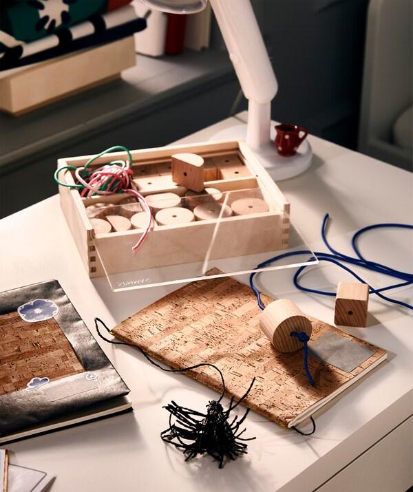 Blat biurka, na którym praca wre: okładki i naklejki nadają książkom osobistego charakteru, a zakładki zrobiono z koralików na sznurku.
