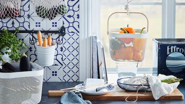 Blat de bucătărie cu diverse legume și fructe păstrate în recipiente suspendate și așezate, precum plasele KUNGSFORS și coșurile RISATORP.