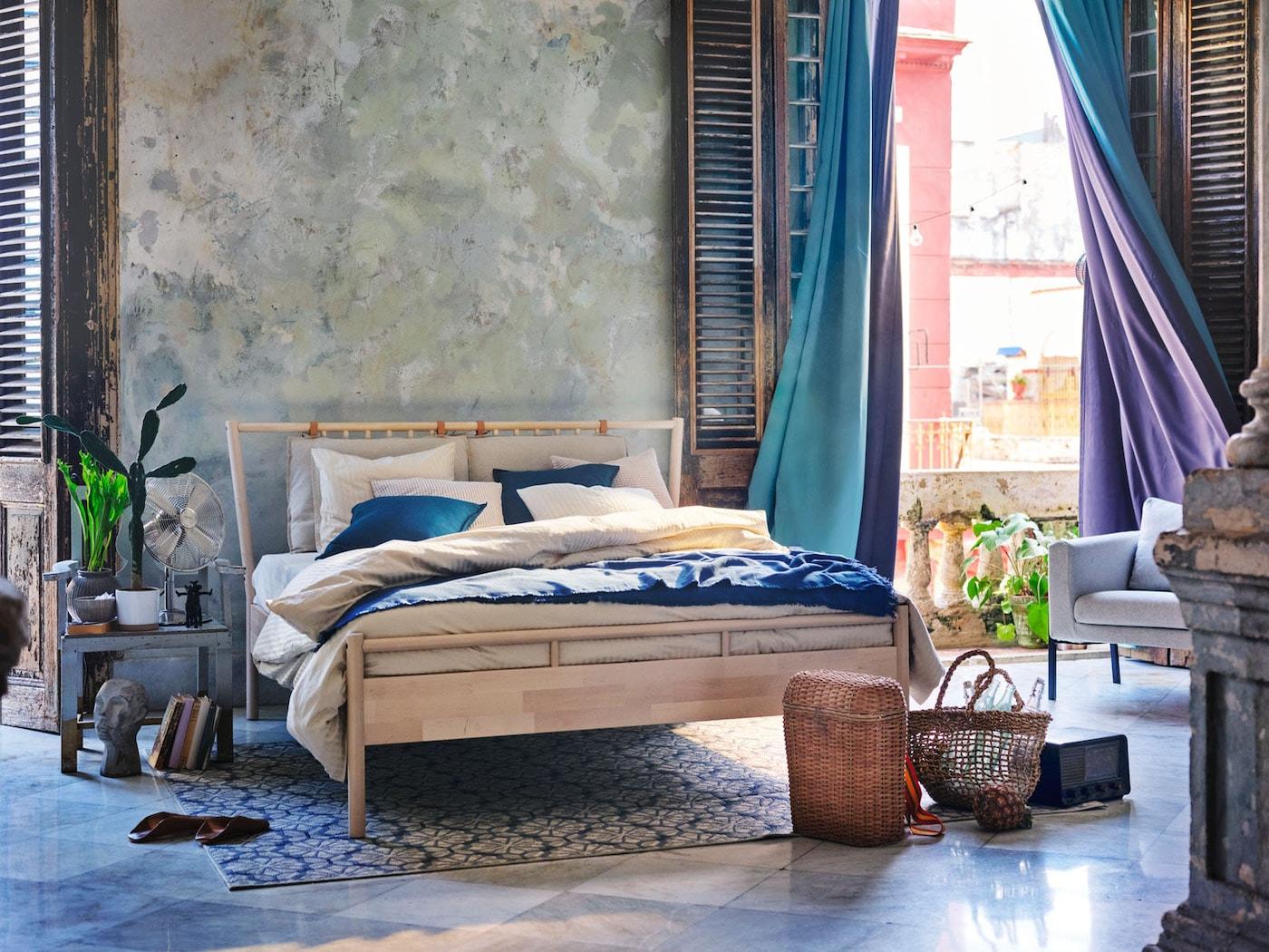 Blåt/gråt soveværelse med turkise og lilla mørklægningsgardiner, der svajer i vinden.